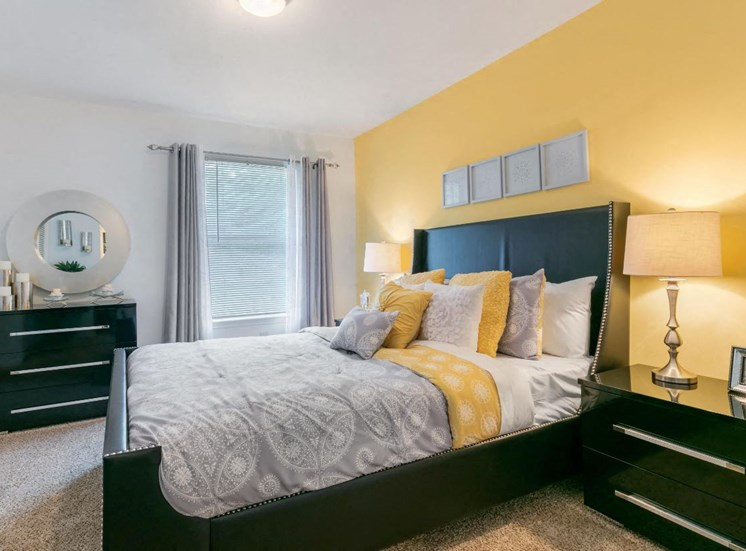 Model Bedroom with Yellow Accent Wall Bed and Nightstands